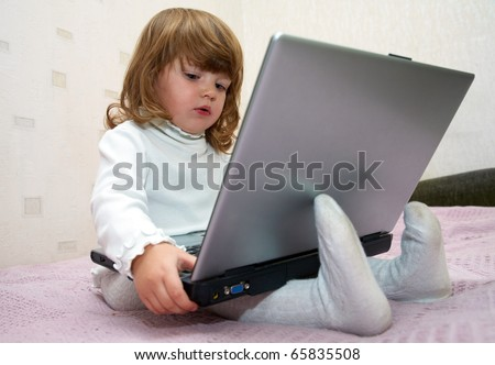 Little girl sitting in front of the monitor laptop at home on the couch. - stock photo