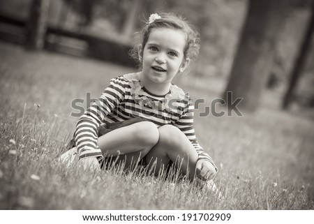 Little girl sitting in grass, black and white or sepia portrait of child - stock photo