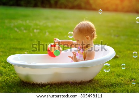 little girl sitting in the bath. - stock photo