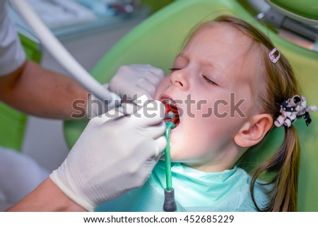 Little girl sitting in the dentists office - dental caries prevention - stock photo