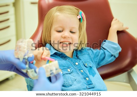 Little girl sitting in the dentists office learning to clean teeth - stock photo