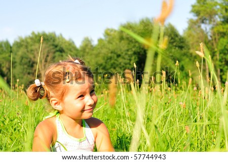 Little girl sitting in the green grass - stock photo