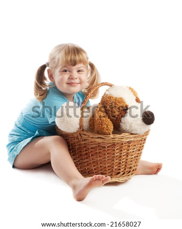 Little girl sitting  near basket with puppy toy