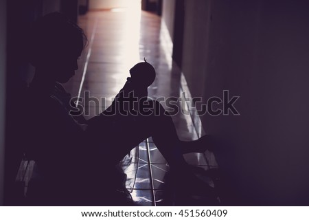 little girl sitting near the wall she sad and depressed,silhouette two color tone. - stock photo