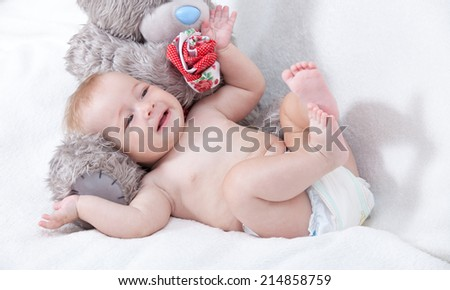 Little girl sitting next to a teddy bear  - stock photo