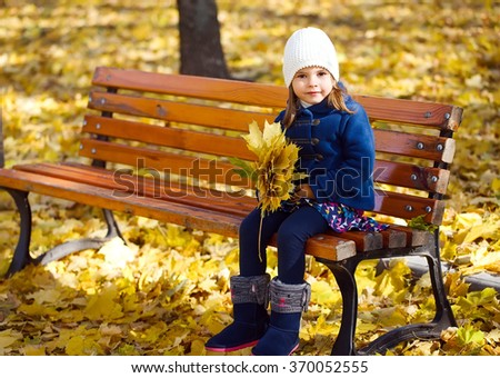 Little girl sitting on a bench in the park - stock photo