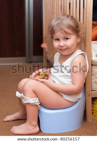 Little girl sitting on a chamber pot in the room - stock photo