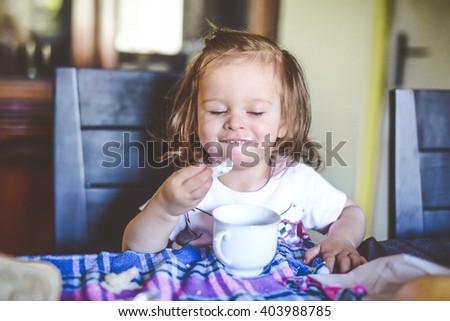little girl sitting on a dining room chair eating breakfast with a dirty face - stock photo