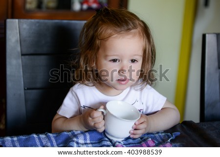 little girl sitting on a dining room chair holding a white cup of milk - stock photo