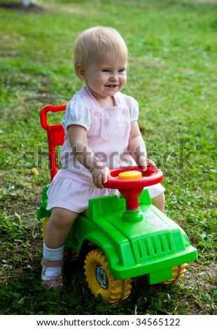 Little girl sitting on a green car