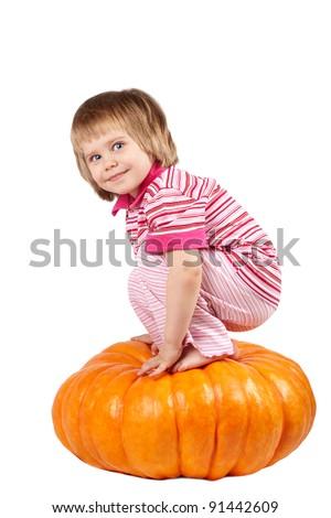 Little girl sitting on a pumpkin - stock photo