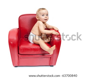 Little girl sitting on a  red armchair. - stock photo