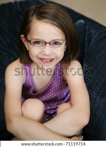 Little girl sitting on a sofa wearing purple eyeglasses - stock photo