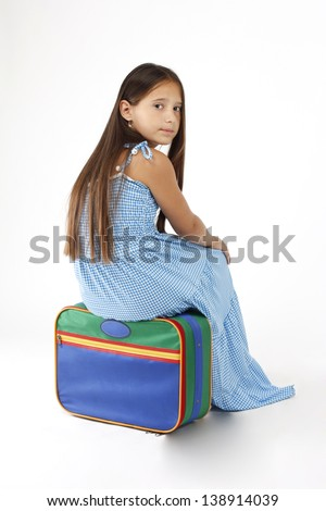 little girl sitting on a suitcase and waiting to embark on the journey