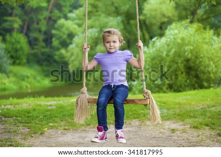 Little girl sitting on a swing in the summer park - stock photo