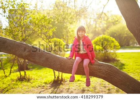 little girl sitting on a tree in the Park. child plays outdoors - stock photo