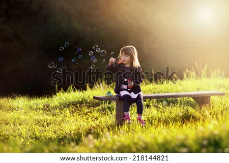 little girl sitting on a wooden bench blows bubbles in the rays  - stock photo