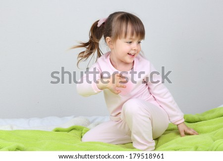 Little girl sitting on bed on wall background - stock photo