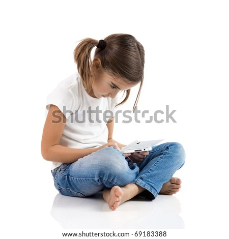 Little girl sitting on floor playing a video-game - stock photo