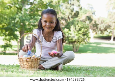 Little girl sitting on grass counting easter eggs smiling at camera on a sunny day - stock photo