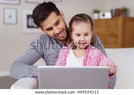 Little girl sitting on her Dads lap as he relaxes on a sofa looking at a tablet computer with a serious expression - stock photo