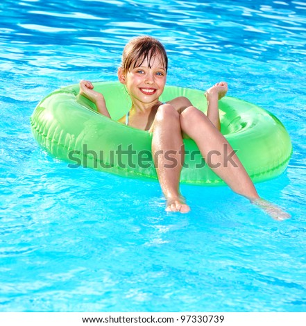 Little girl sitting on inflatable ring in swimming pool. - stock photo