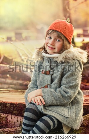 Little girl sitting on logs. Autumn sunlight in a park - stock photo