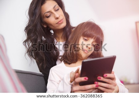Little girl sitting on mother hands and looking at digital tablet. Smooth morning light, casual style - concept of happy family living and family values - stock photo