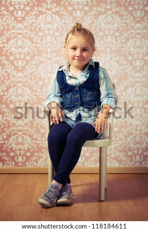 little girl sitting on retro chair