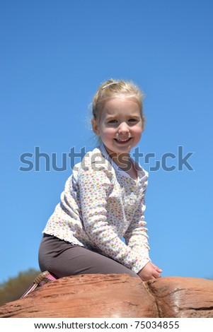 little girl sitting on rock - stock photo