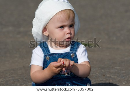 Little girl sitting on sidewalk and holding scrap of paper in her hands. - stock photo