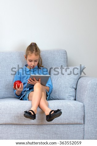 Little girl sitting on sofa and using tablet pc. Space for your text. - stock photo