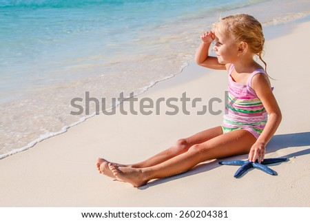 Little girl sitting on the beach in warm sunny day and looking away, relaxation outdoors, summer travel and tourism concept - stock photo