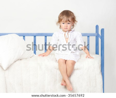 little girl sitting on the bed - stock photo