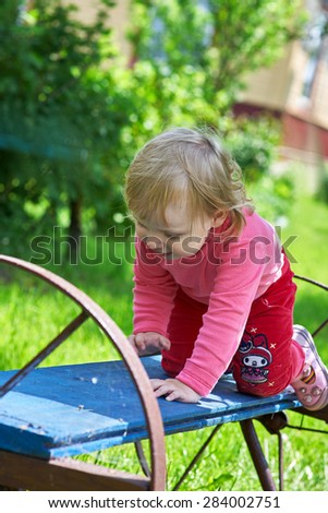 little girl sitting on the bench in park - stock photo