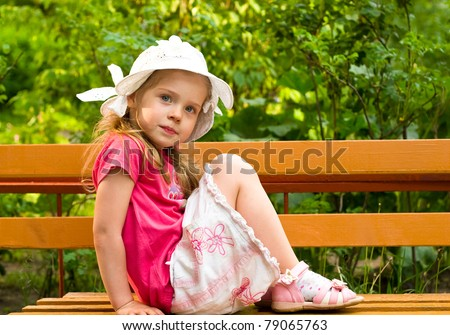 little girl sitting on the bench in park