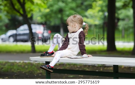 little girl sitting on the bench with a book - stock photo
