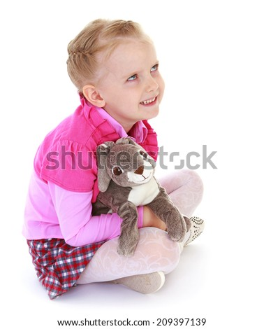 little girl sitting on the floor and holding a toy rabbit on a white background.kindergarten, the concept of childhood and joy, teens - stock photo