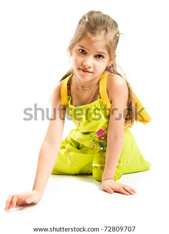 Little girl sitting on the floor and looking at the camera - stock photo