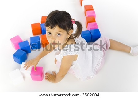 Little girl sitting on the floor and playing colored blocks. Looking at camera, white background. High angle view - stock photo