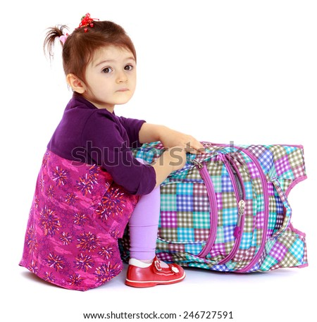 Little girl sitting on the floor and unbuttons knapsack.concept childhood education and child development.Isolated on white background - stock photo