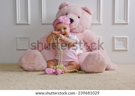 Little girl sitting on the floor holding a pearl necklace - stock photo
