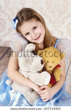 Little girl sitting on the floor holding plush teddy bear - stock photo