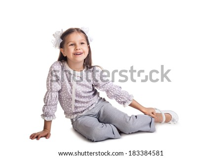Little girl sitting on the floor, smiling and looking up