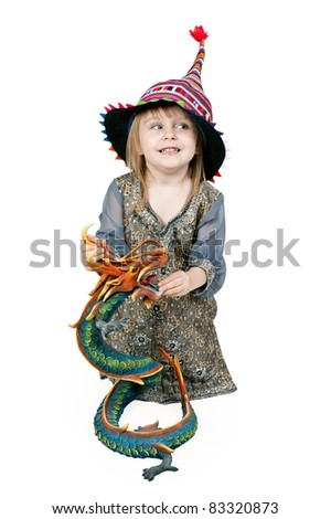 Little girl sitting on the floor with a decorative dragon in the studio is not a white background
