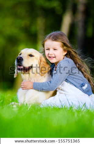 Little girl sitting on the grass with labrador in the summer park