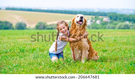 Little girl sitting on the grass with labrador retriever in the summer park. Looking into the camera. - stock photo