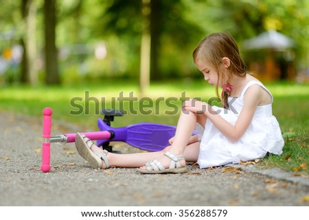 Little girl sitting on the ground after she fell while riding her scooter at summer park - stock photo