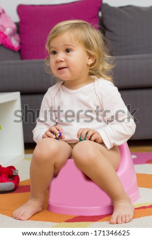Little girl sitting on the potty at home. - stock photo