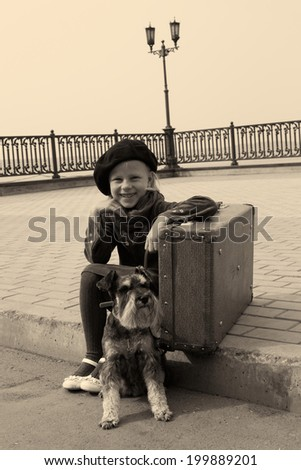 little girl sitting on the road with a dog and a suitcase - stock photo